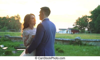 Lovely wedding couple looks on each other and embraces on the nature. Slowly