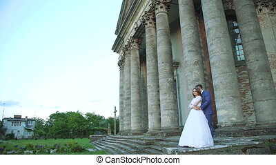 Lovely wedding couple stands in embracess near the castle. Slowly