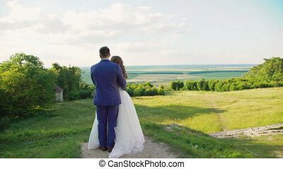 Lovely wedding couple stands in embracess on the beautiful nature 4K