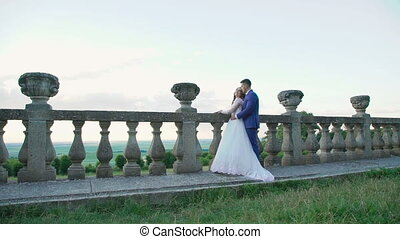 Lovely wedding couple stands in embracess on the castle's balcony. Slowly