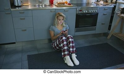 Lovely woman browsing smartphone on kitchen floor -...