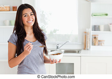 Lovely woman enjoying a bowl of cereals while standing