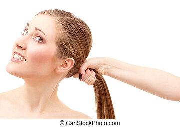 lovely woman face and female hand pulling her hair