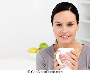 Lovely woman holding a cup of coffee while relaxing