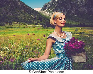 Lovely woman in  blue dress with  basket of flowers against mountain view