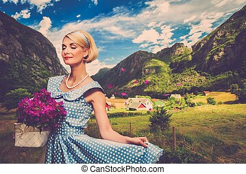 Lovely woman in blue dress with basket of flowers against small village view