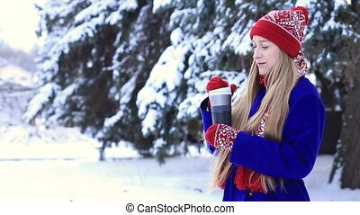 Lovely woman in winter clothes enjoying hot drink