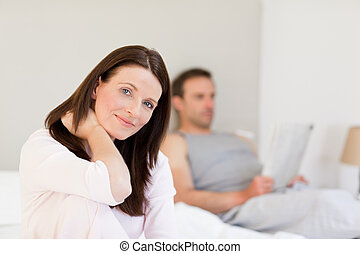 Lovely woman looking at the camera while her husband is sleeping