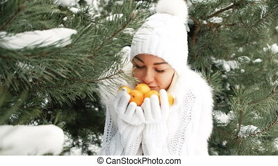 Lovely woman offers tangerines against background of winter landscape
