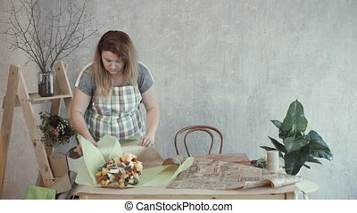 Lovely woman packing edible bouquet in kraft paper - Lovely...