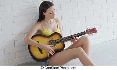 Lovely woman playing guitar on floor