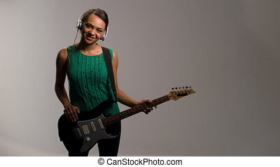 lovely woman plays on guitar and listens to music