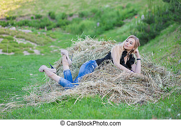 Lovely woman posing sitting on the hay.