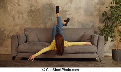 Lovely woman relaxing on sofa with head upside down