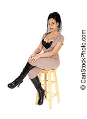 Lovely woman sitting in  beige jumpsuit on chair