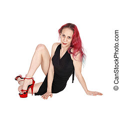 Lovely woman sitting on floor in black dress