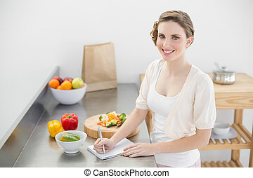 Lovely woman standing in her kitchen writing a shopping list