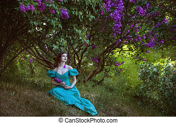 Lovely woman under a bush of lilac.