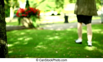 Lovely woman walking through park - Lovely woman walking...