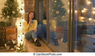 Lovely woman with coffee sitting on windowsill