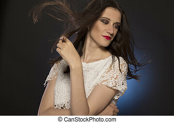 Lovely woman with hair motion at studio