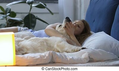 Lovely woman with labrador dog waking up in bed - Lovely...