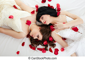 Lovely women posing in wedding dresses with petals