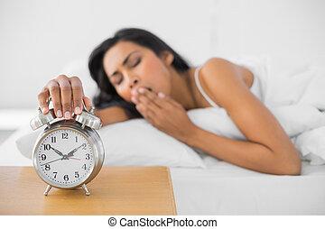 Lovely yawning woman turning off the retro alarm clock lying...