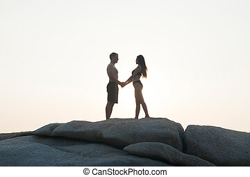 Lovely young adult couple standing on the rocks above tropical sea in isolated.