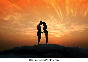 Lovely young adult couple standing on the rocks above tropical sea in Sunset.