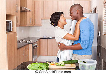 young african couple embracing in kitchen
