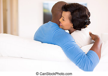 young african couple hugging at home