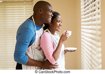 young african couple looking through the blinds