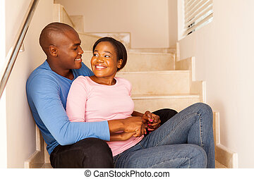 young african couple sitting on steps