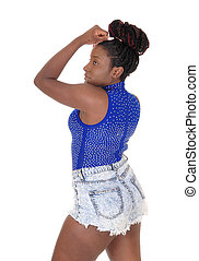 Lovely young African woman standing in shorts in profile