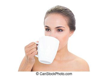 Lovely young brunette woman drinking out of a mug