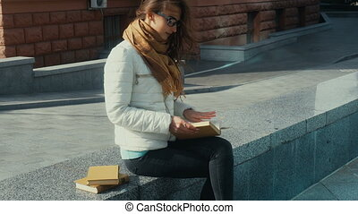 lovely young brunette woman reading a book in the street