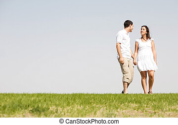 Lovely young couple holding hands and walking
