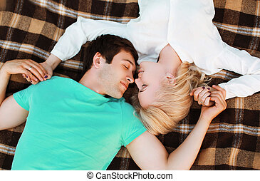 Lovely young couple in love resting on the plaid, warm...