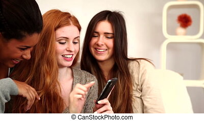 Lovely young friends using smartphone sitting in bright living room