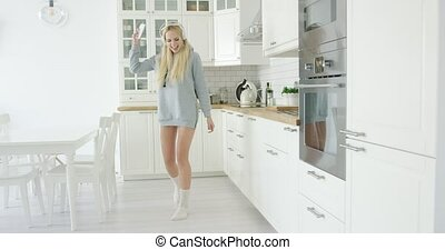 Lovely young girl dancing in kitchen - Cheerful blonde in...