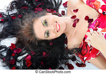 Lovely young girl in petals of roses