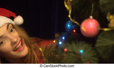 lovely young girl in santa hat having fun with christmas tree