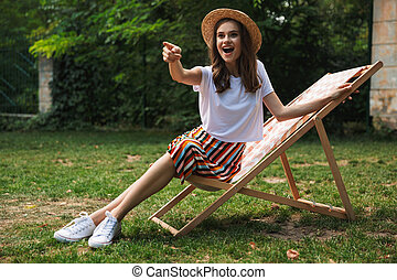 Lovely young girl resting on a hammock at the city park