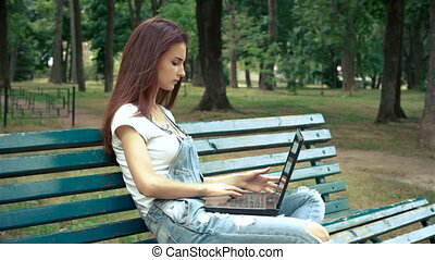 lovely young girl with a laptop in the park sits on a bench