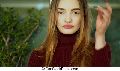 lovely young lady with nice make up looking at the camera at home
