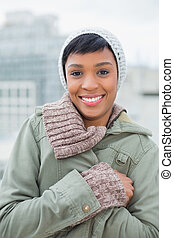 Lovely young model in winter clothes posing and looking at camera outside on a cloudy day