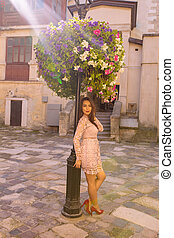 Lovely young model wearing trendy dress, posing near flower bed in rays of light