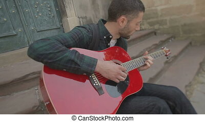 Lovely young street musician with guitar. He makes money with music