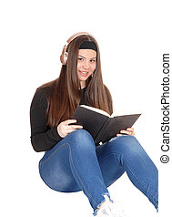 Lovely young teen girl sitting on floor with headphone and reading